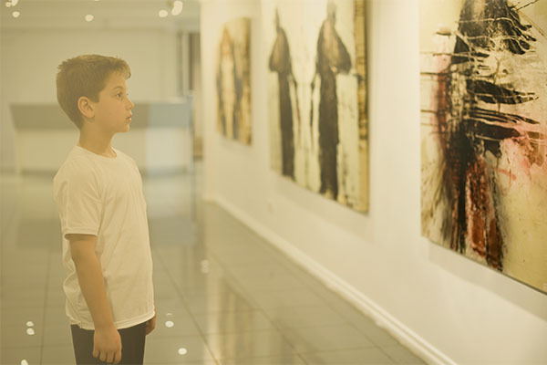 boy looking at art in a gallery