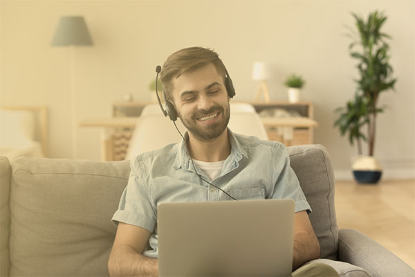 man wearing a headset and working via a laptop