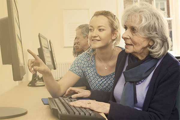 specialist assisting woman at library computer