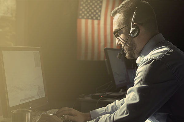 man wearing headset at computer with American flag in background